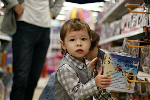 A child holding a box in a toy shop, a parent standing next to him probably wondering –