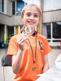 Girl produly showing her victory medal